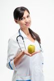 Smiling female doctor holding apple Royalty Free Stock Image