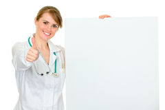 Smiling female doctor holding blank billboard Stock Photo