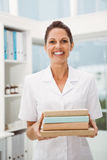 Smiling female doctor holding books in medical office Stock Photography