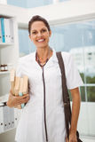 Smiling female doctor holding books in medical office Stock Images