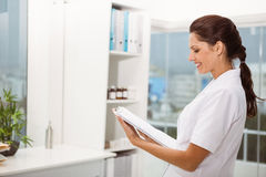 Smiling female doctor holding clipboard in medical office Royalty Free Stock Image