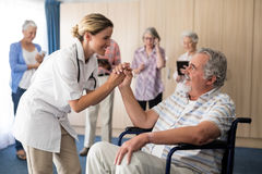 Smiling female doctor holding hands with disabled senior man sitting on wheelchair Royalty Free Stock Images