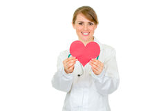 Smiling female doctor holding paper heart in hands. Smiling medical female doctor holding paper heart in hands isolated on white royalty free stock photo