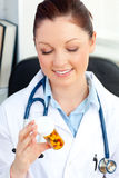 Smiling female doctor holding pills in her office Royalty Free Stock Photography