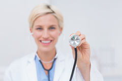 Smiling female doctor holding stethoscope Royalty Free Stock Image