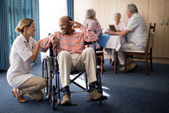 Smiling female doctor kneeling by disabled senior man sitting on wheelchair Royalty Free Stock Photos