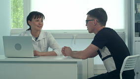 Smiling female doctor listening to male patient in her office stock footage
