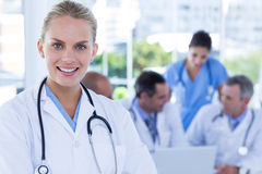 Smiling female doctor looking at camera while her colleagues works Stock Photo
