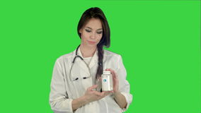 Smiling female doctor looking at camera and holding bottle of pills on a Green Screen, Chroma Key stock footage