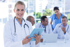 Smiling female doctor looking at clipboard while her colleagues works Stock Image