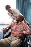 Smiling female doctor looking at disabled senior man sitting on wheelchair against window Royalty Free Stock Image