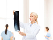 Smiling female doctor looking at x-ray Royalty Free Stock Images