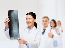 Smiling female doctor looking at x-ray Stock Photo