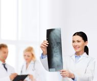 Smiling female doctor looking at x-ray Royalty Free Stock Photos