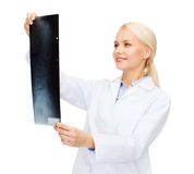 Smiling female doctor looking at x-ray Stock Images