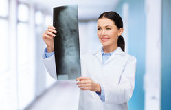 Smiling female doctor looking at x-ray Stock Photography