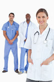 Smiling female doctor with male colleagues behind her Stock Image