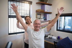 Smiling female doctor and male patient with arms raised Royalty Free Stock Photography