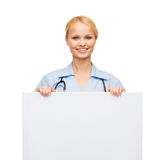 Smiling female doctor or nurse with blank board. Healthcare, medicine, advertisement and sale concept - smiling female doctor or nurse with stethoscope and white Royalty Free Stock Images