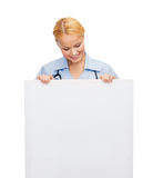 Smiling female doctor or nurse with blank board. Healthcare, medicine, advertisement and sale concept - smiling female doctor or nurse with stethoscope and white Royalty Free Stock Photos