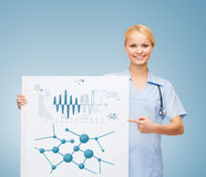 Smiling female doctor or nurse with blank board Stock Photo