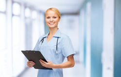 Smiling female doctor or nurse with clipboard. Healthcare and medicine concept - smiling female doctor or nurse with stethoscope and clipboard Royalty Free Stock Image