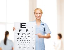 Smiling female doctor or nurse with eye chart Stock Photo