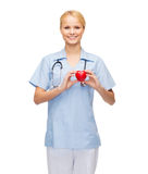 Smiling female doctor or nurse with heart Stock Photos
