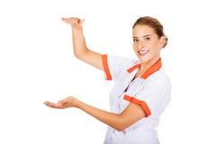 Smiling female doctor or nurse hold something Stock Image