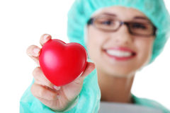 Smiling female doctor or nurse holding heart. Smiling female doctor or nurse in surgical clothes holding red heart stock photo