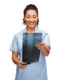 Smiling female doctor or nurse looking at x-ray Stock Photo