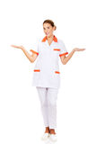 Smiling female doctor or nurse pointing at something Stock Images