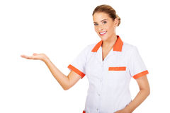 Smiling female doctor or nurse pointing at something Stock Photo