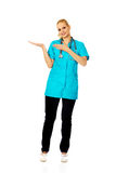 Smiling female doctor or nurse presenting copyspace or something on open palm and pointing for this Stock Image
