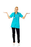 Smiling female doctor or nurse presenting copyspace or something on open palms Stock Photo