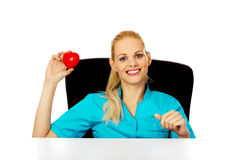 Smiling female doctor or nurse sitting behind the desk and holding heart toy.  royalty free stock photo