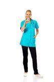 Smiling female doctor or nurse with stethoscope holding syringe Stock Image