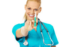 Smiling female doctor or nurse with stethoscope holding syringe Stock Photos