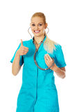 Smiling female doctor or nurse with stethoscope showing thumb up Royalty Free Stock Photo