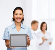 Smiling female doctor or nurse with tablet pc. Healthcare, medicine and technology concept - smiling african american female doctor or nurse with tablet pc Stock Photo
