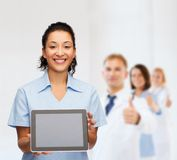 Smiling female doctor or nurse with tablet pc Stock Images