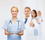 Smiling female doctor or nurse with tablet pc. Healthcare, medicine and technology concept - smiling female doctor or nurse with tablet pc computer Royalty Free Stock Photos