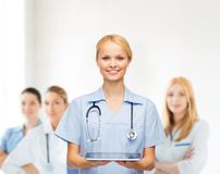 Smiling female doctor or nurse with tablet pc. Healthcare, medicine and technology concept - smiling female doctor or nurse with tablet pc computer Royalty Free Stock Image