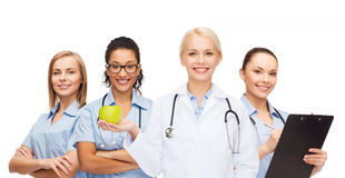 Smiling female doctor and nurses with green apple Royalty Free Stock Image