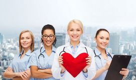 Smiling female doctor and nurses with red heart Royalty Free Stock Photo