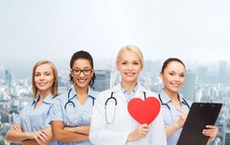 Smiling female doctor and nurses with red heart Stock Image