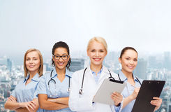 Smiling female doctor and nurses with tablet pc Stock Photography