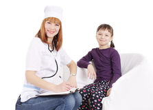 Smiling female doctor pediatrician and girl sitting Stock Photography