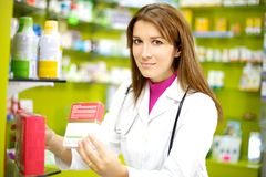 Smiling female doctor in pharmacy with medicine Stock Image