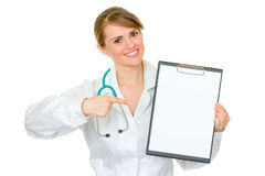 Smiling female doctor pointing on blank clipboard Royalty Free Stock Images
